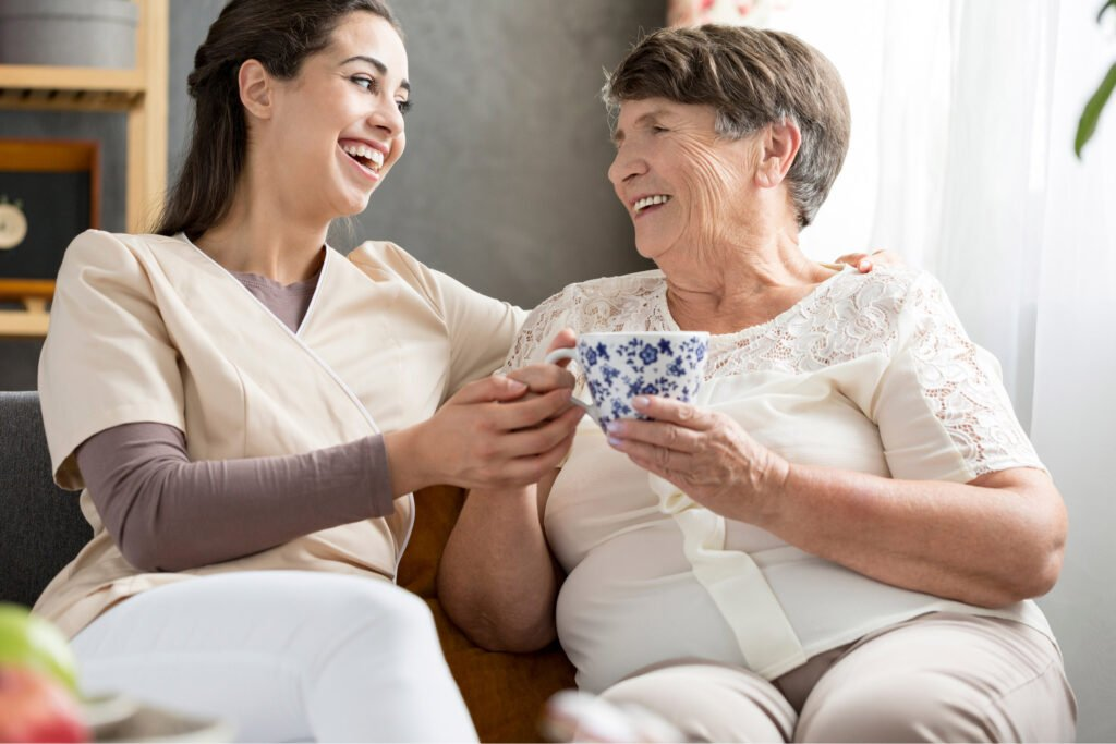 older and younger woman smiling and sat close to each other. Atwell Care Ltd. Live in care. Home Care. Care Company. Bath. Frome. Keynsham. Saltford.