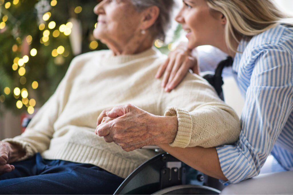 Old woman sat in wheelchair holding hands with crouched smiling younger woman. Atwell Care Ltd. Live in care. Home Care. Care Company. Bath. Frome. Keynsham. Saltford.