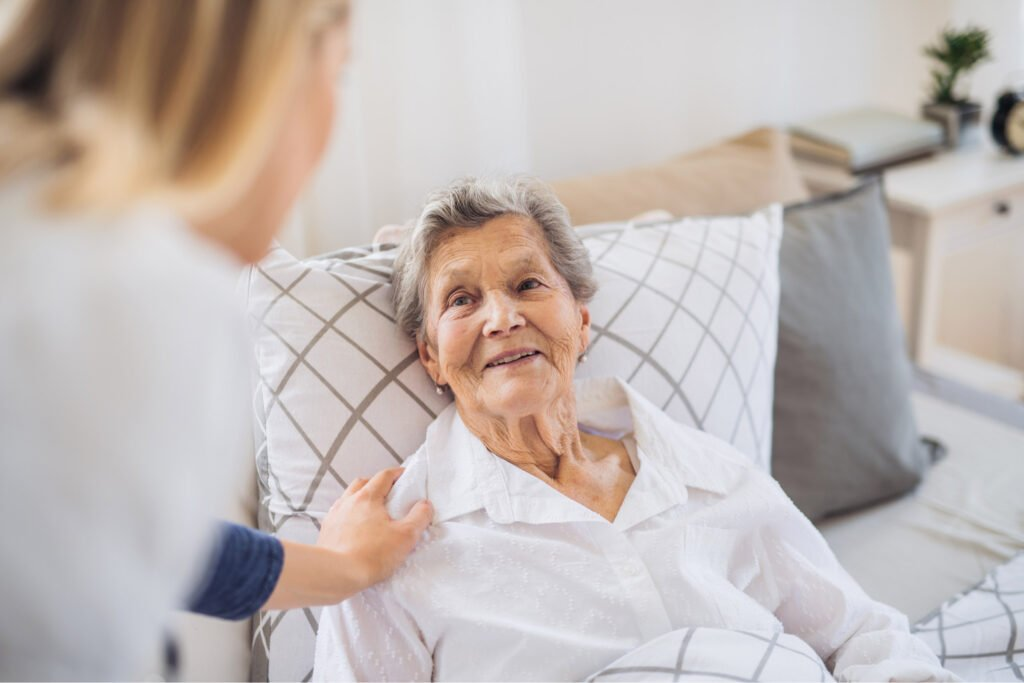 Smiling woman laying on her bed, looking at woman in front of her. Atwell Care Ltd. Live in care. Home Care. Care Company. Bath. Frome. Keynsham. Saltford.