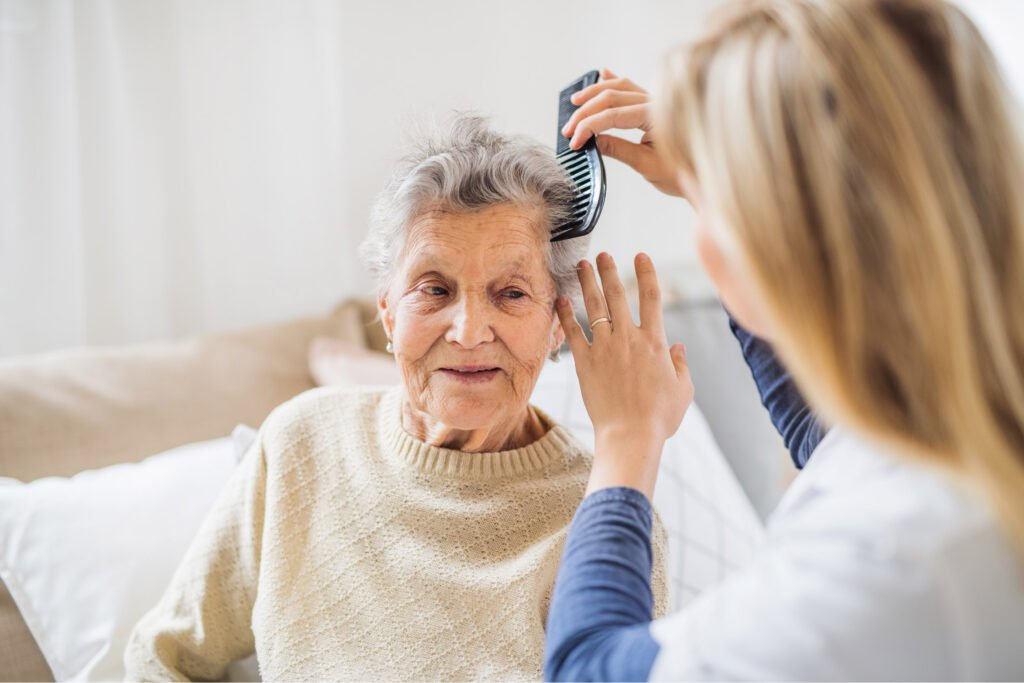 Happy old woman having her hair combed by younger woman. Atwell Care Ltd. Live in care. Home Care. Care Company. Bath. Frome. Keynsham. Saltford.