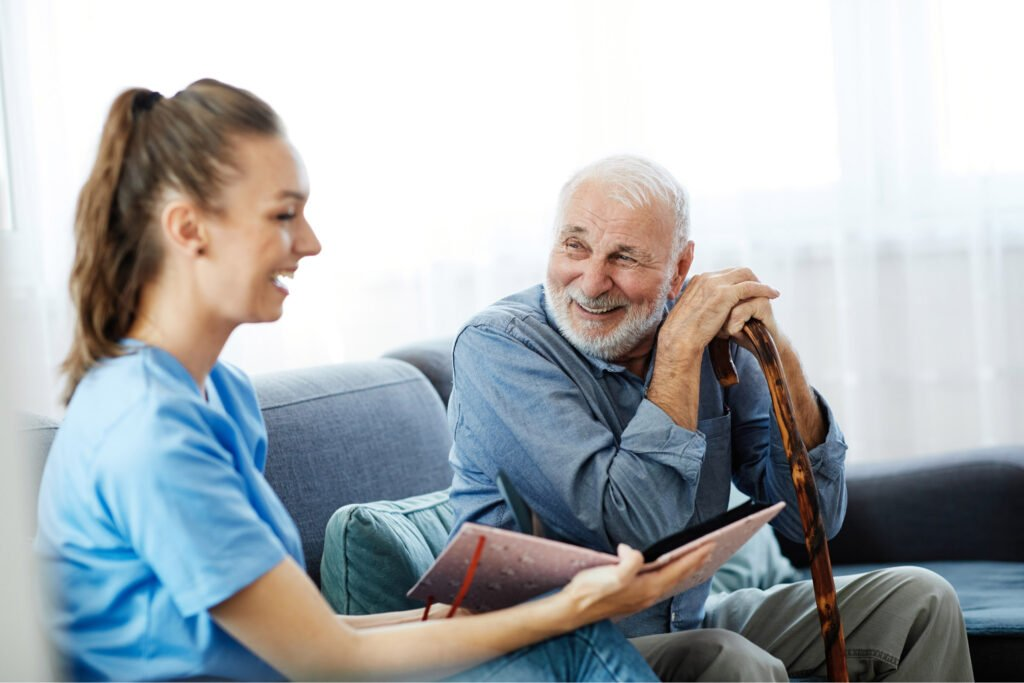 Happy old man sat on sofa, leaning on walking stick, next to a young woman carer who is smiling. Atwell Care Ltd. Live in care. Home Care. Care Company. Bath. Frome. Keynsham. Saltford.