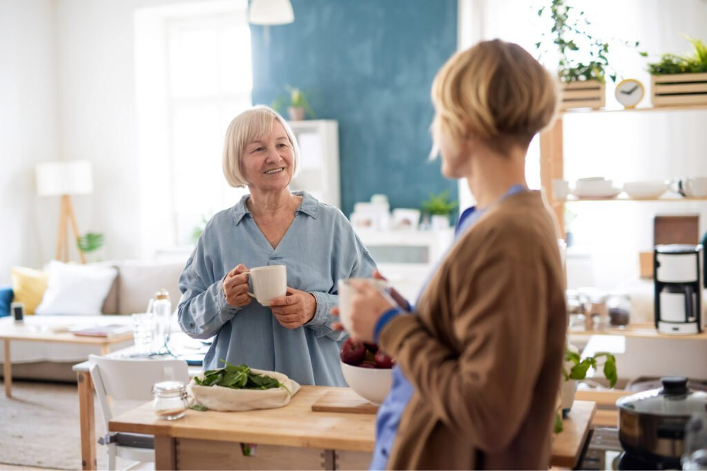Adult mother and daughter holding mugs in the kitchen. Atwell Care Ltd. Live in care. Home Care. Care Company. Bath. Frome. Keynsham. Saltford.