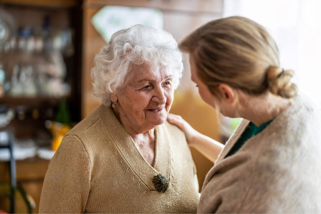 Old woman with beige jumper and short white hair, younger woman facing opposite, out of focus. Atwell Care Ltd. Live in care. Home Care. Care Company. Bath. Frome. Keynsham. Saltford.