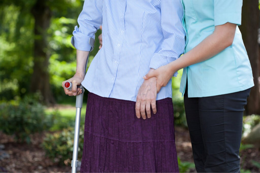 Young woman carer helping older woman walk with walking stick. Atwell Care Ltd. Live in care. Home Care. Care Company. Bath. Frome. Keynsham. Saltford.